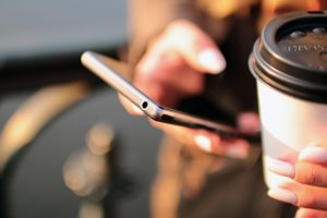 This is a picture of someone holding a cup of coffee and their phone.
